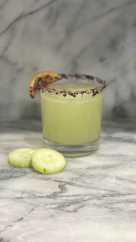 cucumber drink with a lime garnish and hibiscus salt rim on a marble background